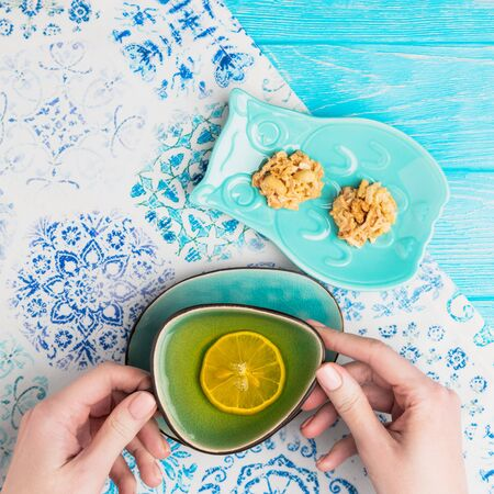 Female hands holding a turquoise cup of lemon tea