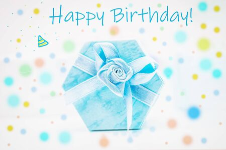 Birthday greeting card. Blue gift box on a festive colored background, vertical photo