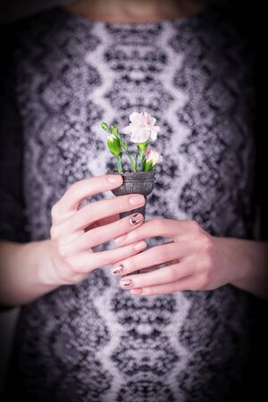 Female hands holding pale pink carnation flowers in black waffle cone on a black and white dress. Snake skin texture