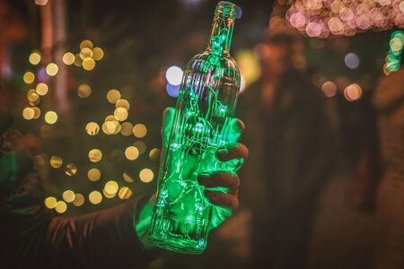 Magic Christmas. Green garland in the transparent bottle. Garland in the hand, toned photo
