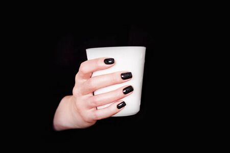 Beautiful female hands holding white cup on a black background. Manicure with black nail polish. Copy space Reklamní fotografie