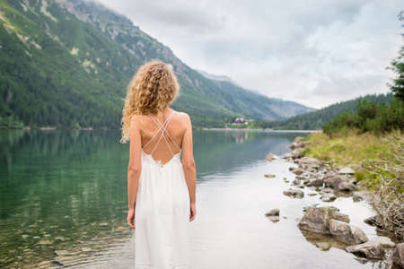 Beautiful young woman with curly hair in a white dress stands near incredible lake. Tatra National park, Poland. Famous lake Morskie Oko or Sea Eye
