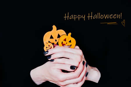Happy Halloween, halloween card. Female hands holding funny pumpkins on black background. Manicure with black nail polish 写真素材