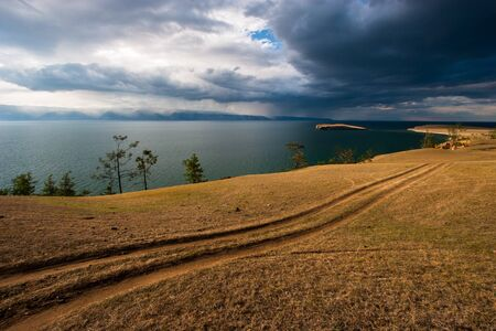 Steppe road on the shore of Lake Baikal. In the lake is an island. Rain clouds in the sky. Behind the lake are mountains over which it rains. Shades of yellow and blue.