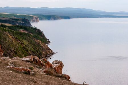 The rocky shore of Lake Baikal with protruding stones and red moss on them. The shore is overgrown with forest. Away the haze.
