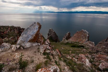 Rocks Three Brothers on the island of Olkhon on Baikal lake. Sky with clouds. On the stones is red moss and green grass around. It is raining in the distance, mountains are visible.