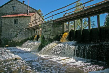 Dam at the old water mill made of stones. Beautiful streams of water, a small waterfall. Over the dam is an old wooden bridge. Blue clear sky. Zdjęcie Seryjne