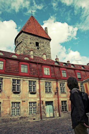 A man stands with his back and looks at an old beautiful building with red tiles in the old city of Tallinn. The walls are yellow shabby. Blue door. Beautiful old tower of limestone. The sky is blue with clouds. Tinted in yellow.