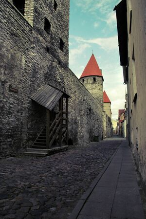 City street of the old city in Tallinn with an ancient wall of limestone and red tile roofs on the towers. The street is narrow. There is a passage in the wall with a staircase. The road from the cobblestone. Tinted in yellow.