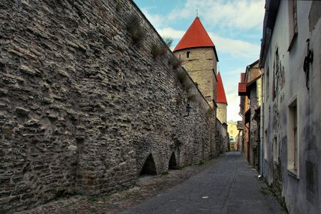 The road next to the old city defense wall in the city of Tallinn. The wall collapses. On the roofs of the towers red tile. Standard-Bild - 129230697