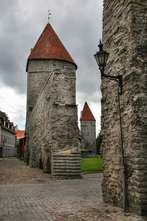 Passage in the city defense wall of Tallinn. On the roofs of the towers red tile. The second tower is visible in the aisle. Hanging a vintage lantern to illuminate the street. In the sky clouds. On the road cobblestones.