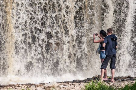 Tourists take pictures of the waterfall very close. Much water. Powerful flow. The water is blurry.