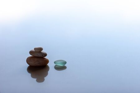 Minimalism. 3 pyramid pebbles and a green glass with reflections. Blue blurred background. Selective focus. Place for text.