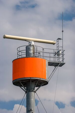 Radar with transmitter on a round steel pillar against the sky. In the sky clouds. Tensioned cables hold a pole.