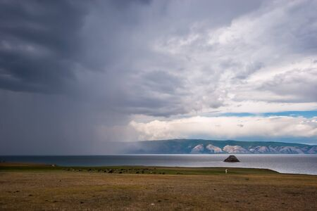 Rain over Lake Baikal and the cows on the shore on a cloudy day. Over the rain and the lake you can see the mountains. On the sky heavy lead clouds. It rains like a wall.
