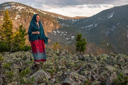 Beautiful cute girl in a dress and a scarf stands on large stones in the mountains. Against the background of mountains with snow overgrown with forest. Selective focus on the girl.