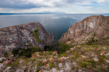 View between two rocks on Lake Baikal from Olkhon Island. On the stones is red moss, near the vets and grass. Mountains behind the lake. Clouds in the sky. There is a dry tree and green.