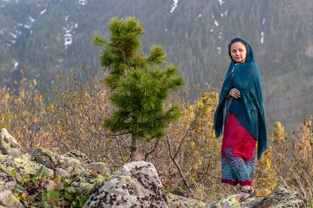 A nice girl in a dress and shawl stands on large stones next to a young conifer in the mountains. Against the background of mountains covered with coniferous forest. Selective focus on the girl. Zdjęcie Seryjne