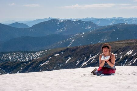 A girl sits in the snow in a sundress on the snowy peak of the mountain and holds snow in her hands. The girl is smiling. Against the background of many beautiful mountains.