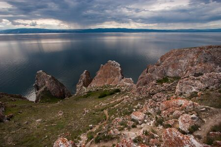 Three Brothers Rocks on Olkhon Island on Lake Baikal. Huge stones on the background of the lake. In the water, a beautiful reflection of the sky. Behind the mountain lake. The sky with clouds. Zdjęcie Seryjne