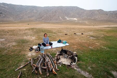 Girl tourist sitting in a yoga pose on a tourist silver rug by the fire. Behind the mountains. Nearby is a gas burner and a gas cylinder. Firewood has been prepared for the fire. The bonfire is lined with stones. Copy space.