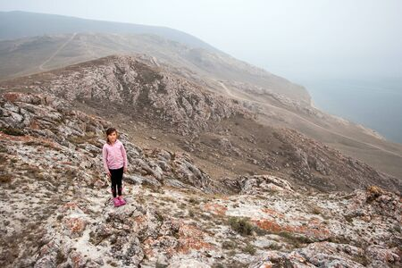A young girl tourist stands on the edge of a high cliff on the shore of Lake Baikal. Girl looking at the camera. The cliffs are red covered with moss. The weather is foggy. 스톡 콘텐츠