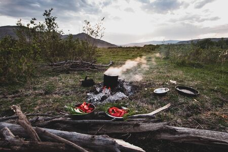 A boiling pot with steam is standing on a fire of a bonfire and next to it are plates with fresh vegetables. In the plates are red tomatoes, cucumbers and onions. Tourist idyll on a background of mountains. Copy space. Banco de Imagens