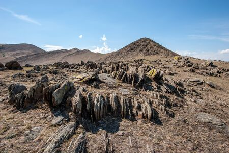 Beautiful flat sharp stones stick out of the ground on a hill vertically. Stones are everywhere. Mountain range. Blue sky. Фото со стока