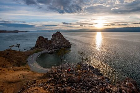 Sunset on Lake Baikal overlooking the high cliff of Shamanka and beautiful sky. There are stones and several trees on the shore. There are clouds in the sky. Solar path on the water and small waves. 免版税图像