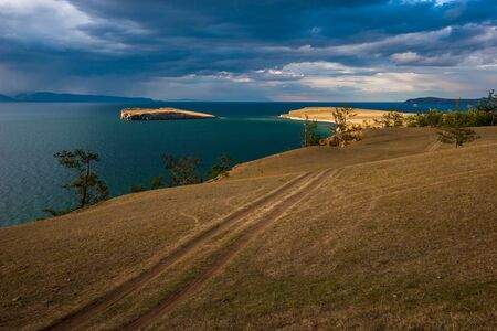 View of the island on Lake Baikal across the steppe with a field road in cloudy weather with the sun. Trees grow on the edge of the shore, on the horizon there are mountains. Heavy clouds in the sky. 스톡 콘텐츠
