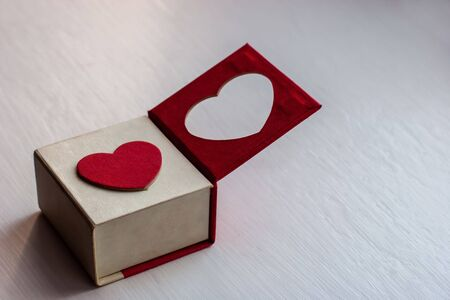 White gift box with a red heart on the lid for a romantic gift for girls on a painted wooden surface. One half of the lid is open. The heart is cut in the lid. Magnet cover. Copy space.
