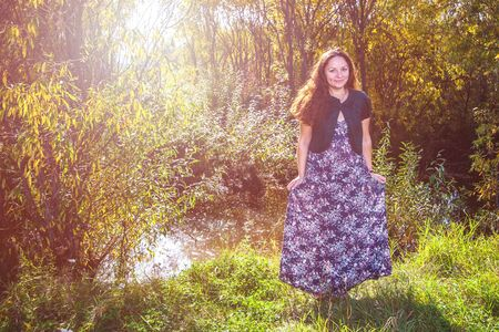 Portrait of a smiling girl in a colored dress illuminated by the rays of the sun in a deciduous forest. Cute European face, long dark hair. Hands hold a dress in flowers. Everything is bathed in the sun.