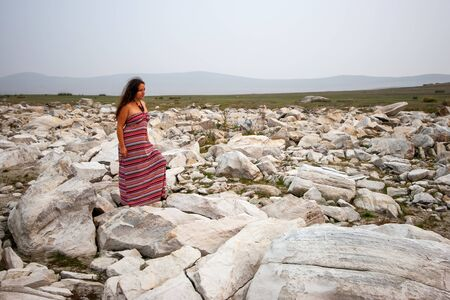 A beautiful tanned European girl in a red dress with long dark hair stands on white stones in the steppe. Hills in the fog and gray sky. Copy space. Фото со стока