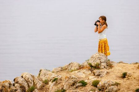 A girl with binoculars in her hands stands on Lake Baikal on the rocks and looks over the binoculars. Big stones. T-shirt and colored yellow skirt. Selective focus on the girl. Stock fotó - 132748007