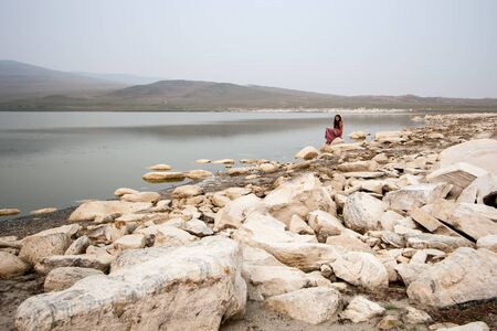 A girl sits on a stone by the lake like a mermaid. Steppe with hills and a lake in the fog. A lot of big white stones on the shore. The gray sky is foggy. Copy space.