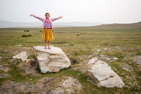 Satisfied child girl stands with arms spread out on a stone on a field with green grass. Pink jacket and yellow skirt. Hills on the horizon in fog and gray sky. Green grass around. Copy space. Stok Fotoğraf