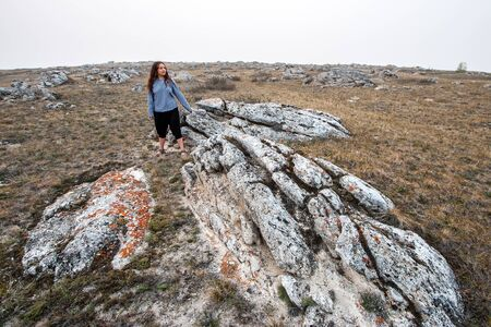 A girl with dark long hair in a marine vest stands at the huge stones sticking out of the ground. On the stones is red moss. Sparse grass of the earth. The sky is gray with fog.