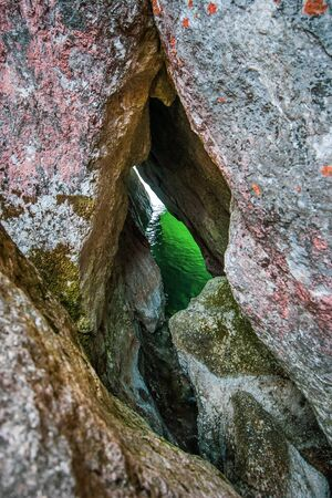 Green water is visible through a narrow gap in a granite rock. Moss on stones. Vertical frame.