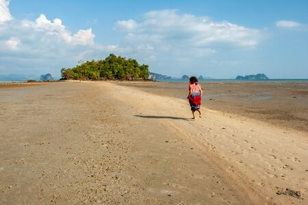 A girl runs along a sea spit to an island with green trees during a low tide. There are clouds in the sky, sunny. Rocks are visible in the sea.