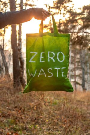 Zero waste concept. Textile green bag with a white inscription in hand on a background of nature and the sun. Against the background of blurry trees and autumn grass. Vertical. Copy space below.
