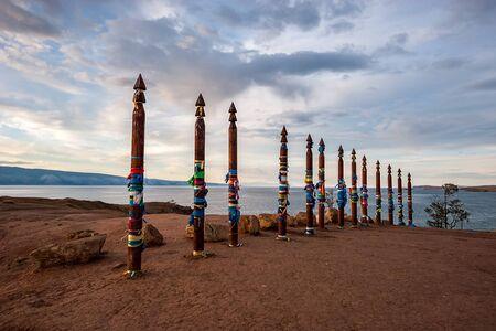 Sacred pillars with tied ribbons on Cape Burhan of Olkhon Island. Buryat traditions. Shamanistic rites of Lake Baikal. Imagens