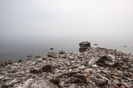 Stones on the lake in the fog. The fog is like milk. Copy space on top.