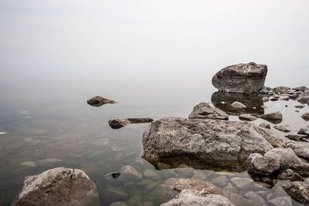 Fog above the water on a lake with large stones. Clear water with green stones. White milk background. Copy space on top.