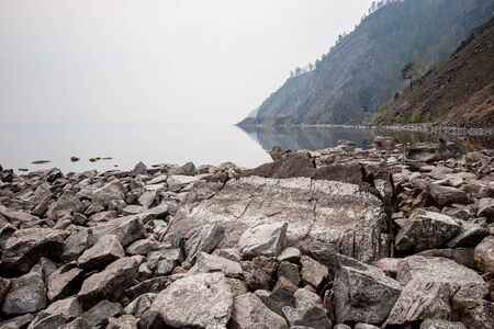 A rock by the lake in fog and large stones by the water. There are trees on the rocks. The stones are gray. Copy space.