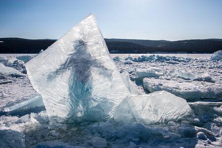 Ein riesiges Eisstück, das im Baikalsee eingefroren ist, hinter dem ein Mann steht. Klarer Himmel, Hügel hinter einem See mit Schnee und vereinzeltem Eis.