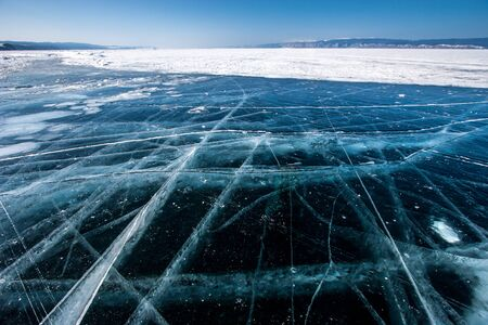 Transparent ice on Lake Baikal with large beautiful cracks on a sunny day. In the distance is snow on ice and mountains on the horizon. Stock fotó