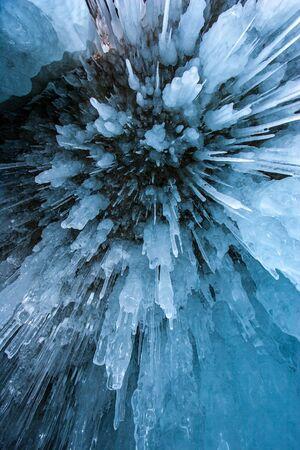 Natürlicher struktureller Hintergrund. Von der Decke der Höhle hängen spitze blaue Eiszapfen. Ansicht von unten. Vertikale Ausrichtung.