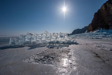 An ice hole and ice cubes from it piled into the wall on a sunny day. Clear blue sky with the sun. Big rock nearby.