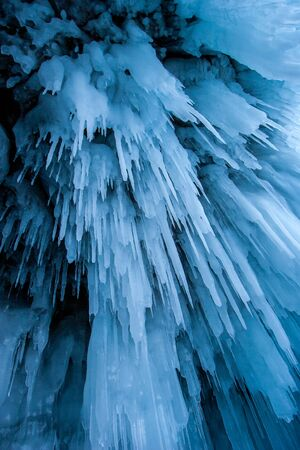 Eiszapfen aus blauem Eis in einer Höhle am Baikalsee. Lange Eiszapfen hängen wie Stalaktiten. Vertikal.