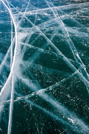 Long cracks on the transparent ice of Lake Baikal. Many cracks in thick ice. Vertical orientation. Imagens